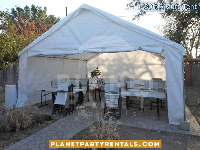 20 x 20 Tent with Side panels, white rectangular tables and white Plastic Chairs on Cement